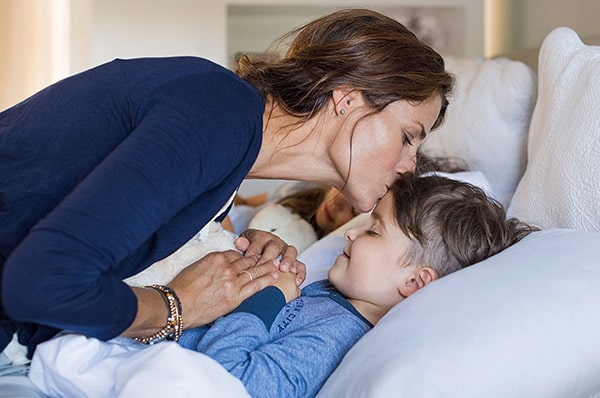 woman kissing son goodnight