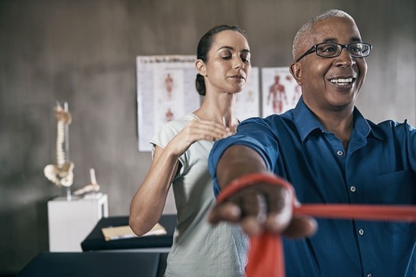 physical therapist working with man
